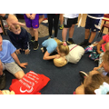 Pupils in 4H performing CPR on a manikin.