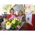 Our head girl presenting flowers to Marion
