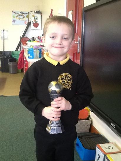 George proudly showing his trophy for playing football.