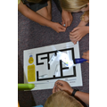 Children using the law of reflection to solve the light maze in Science.