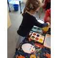 Mixing colours to decorate an egg.