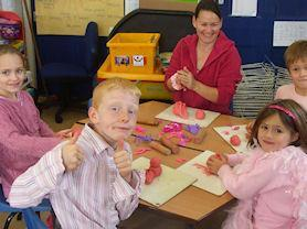Mrs Rowe helping with some pink play dough.