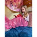 Reading in her cosy den.