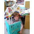 Matthew reading in his superhero den.