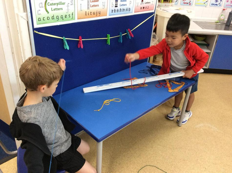 Measuring the strings of the harp using the ruler...we chose this independently!
