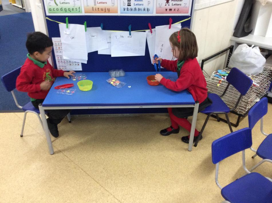 Using pom poms and tweezers to develop our fine motor skills