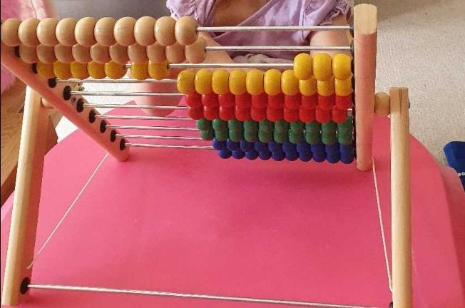 Practising taking away using an abacus!