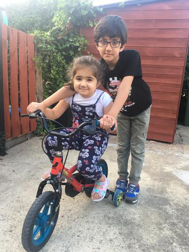 Helping his sister to ride a bike.