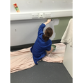 Using a paint brush to paint the walls.