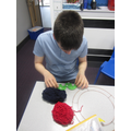 This is the children using pom pom makers to create door wreaths.