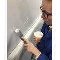 Using polyfila to fill holes in the wall.