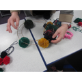 Using a hot glue gun they glued the pom poms into a wire to create the wreath.