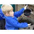 Using the mud kitchen to make tasty treats.