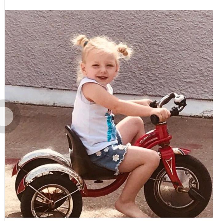 Annie enjoying the sun on her bike!