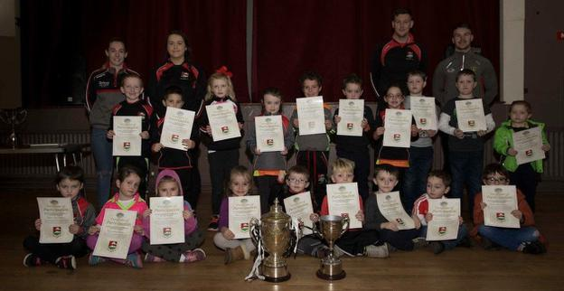 The Dundrum U-8 team and management alongside special guests Darragh O'Hanlon and Chara Laverty. Also included in the photo is the Down SFC and JFC trophies which were won by Kilcoo and Dundrum respectively this year.