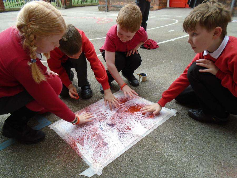 The children have a go at spraying handprints.