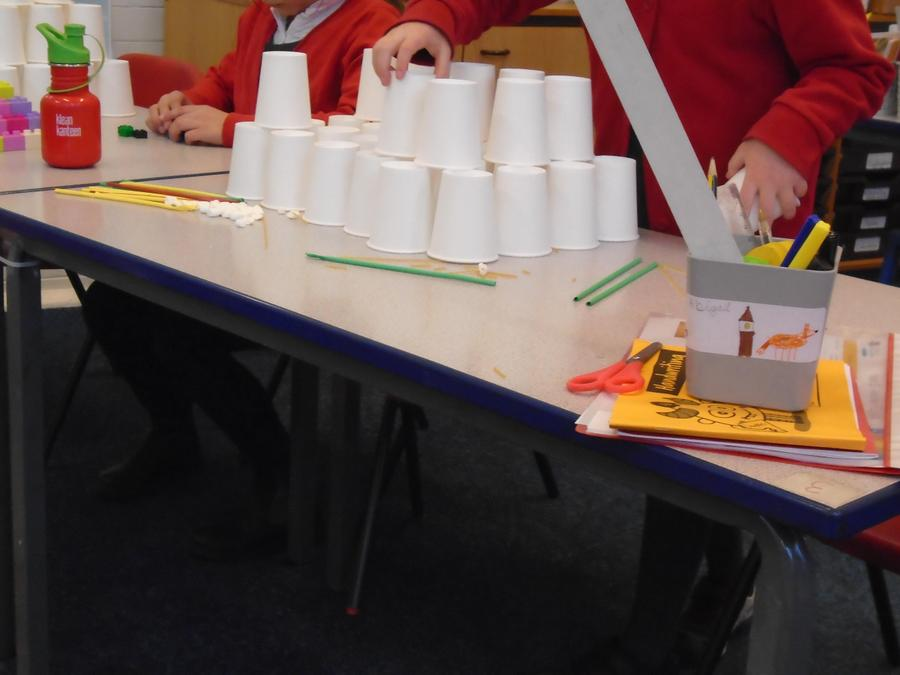 Abi thought carefully when building a pyramid out of cups.