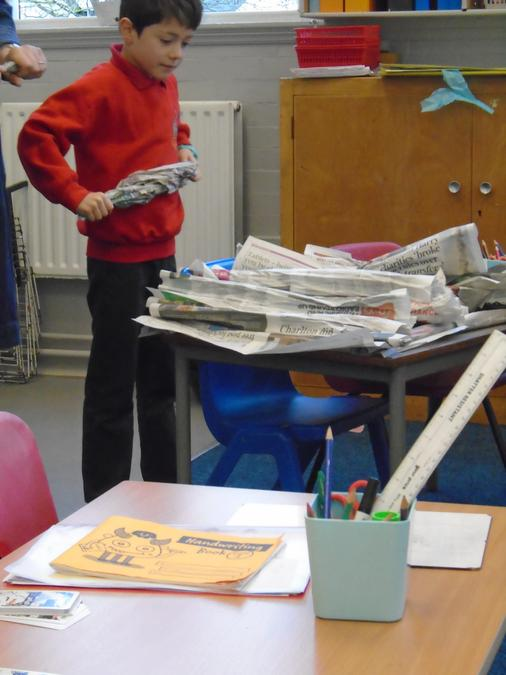 The start of making a large newspaper pyramid.
