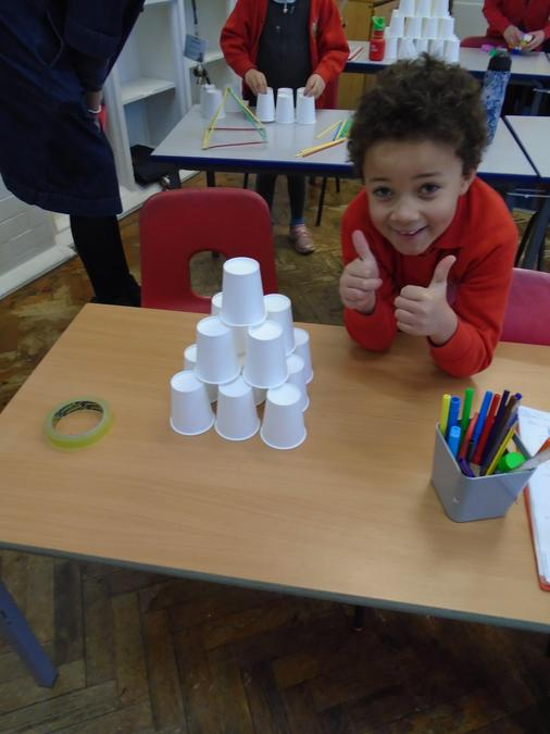Carefully constructed step pyramid using cups.