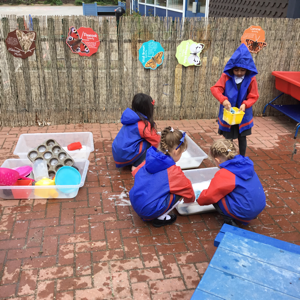 Cleaning the utensils in the mud kitchen!