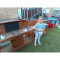 Olivia in our mud kitchen.