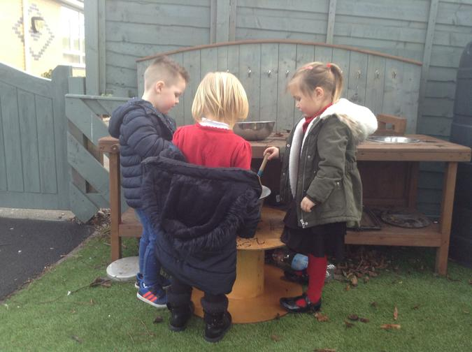 Making cakes in the mud kitchen.