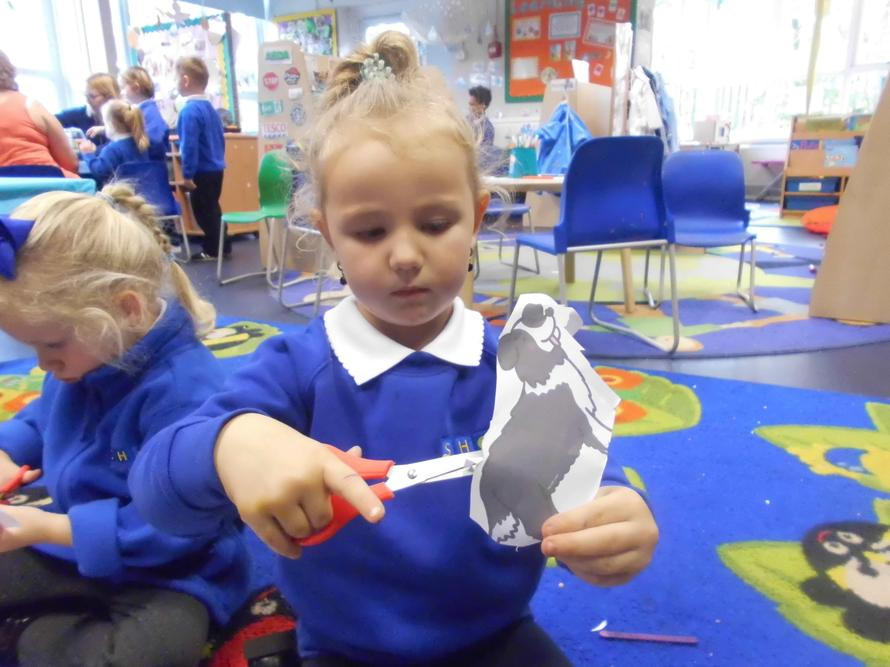 Kylie carefully cutting her puppet out!