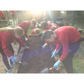 Year 5 and 6 children prepare their class' vegetable bed for planting.