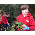 Cameron, along with other children from Woodlands Class tidy the Peace Garden.