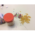 Wrapping loom bands around fusilli pasta.