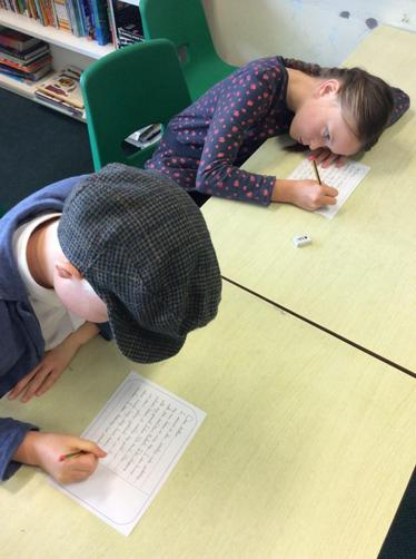 These children are writing a postcard to their family.