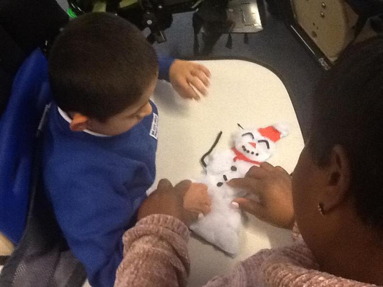 Decorating his snowman