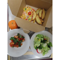 Homemade Pizza with freshly prepared Tomato and Basil salad and whole fruit