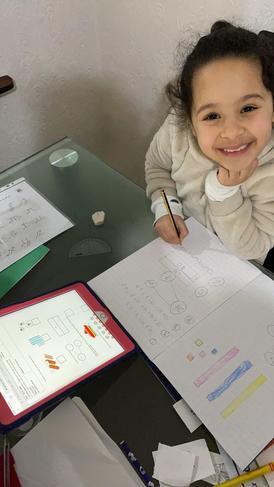 Sadaf working happily on her maths work