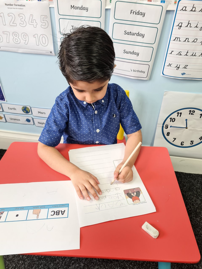 Hasnain writing his Jack and the Beanstalk story.