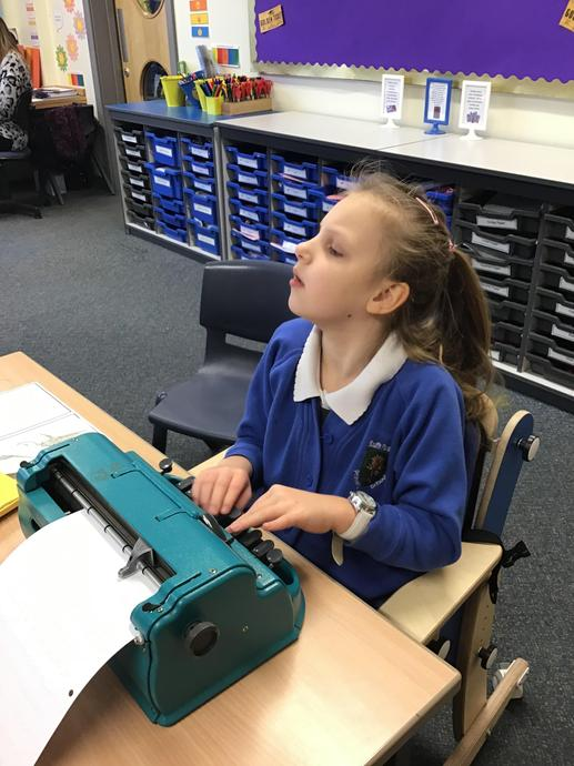[Picture of child using Perkins Braille Machine in classroom]