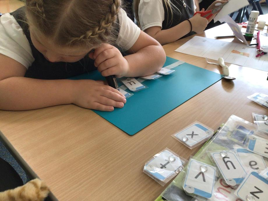 [Picture of child using RNIB Penfriend and using tactile phonics resources]