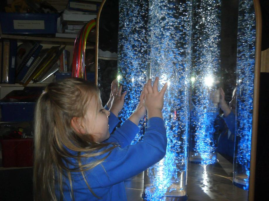 [Picture of child looking at bubble tube]