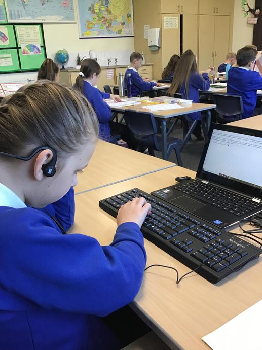 [Picture of child using assistive technology independently in class.]
