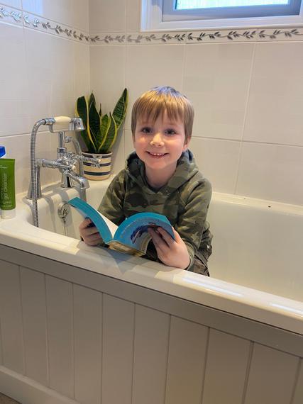 Thomas reading in the bath