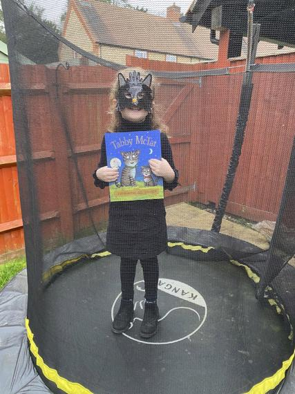 Tabby Mc Cat aka Macie reading on the trampoline