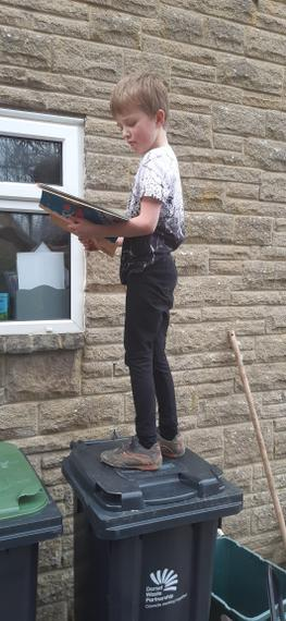 Leo reading whilst balancing on a bin
