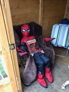 Spiderman aka Jack reading in the summer house