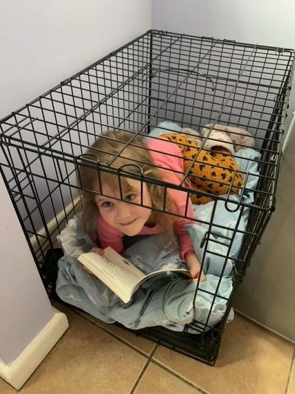 Esme reading in her dog's crate