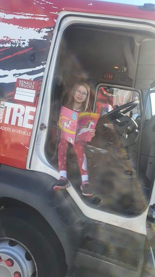 Jazmine reading in her Daddy's truck