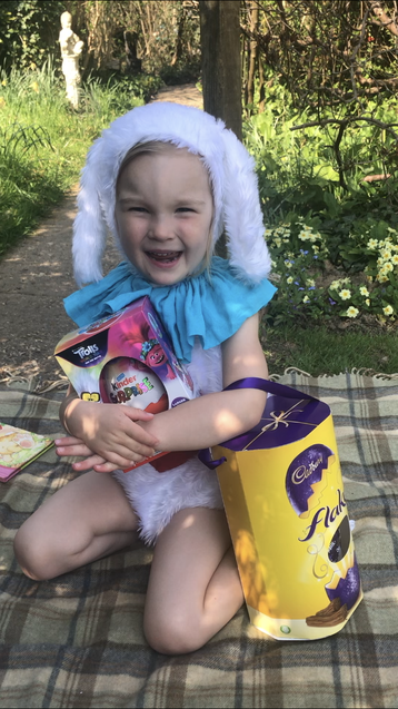 The Easter Bunny in the garden with chocolate eggs