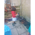 Thenuki watering the plants in her garden