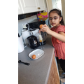 Aisha is cracking the eggs for the cake mixture.