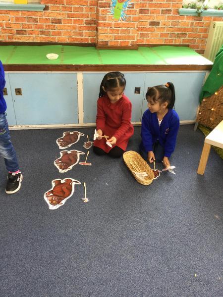 Amirah and kaviya use stick puppets to story.