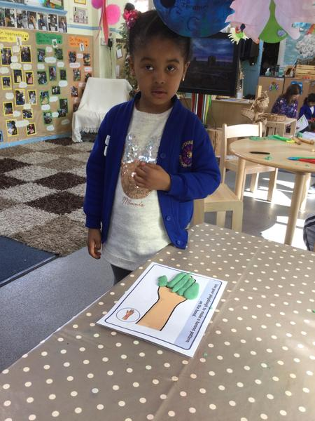 Amira makes a playdough mendhi pattern.